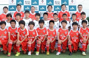 贈呈されたユニホームを着たロアッソ熊本ジュニアの選手ら。最後列はJAグループ熊本の常勤役員ら=21日、熊本市