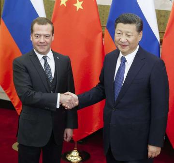 中国の習近平国家主席と握手するロシアのメドベージェフ首相(左)=2017年11月1日、北京の釣魚台迎賓館(共同)