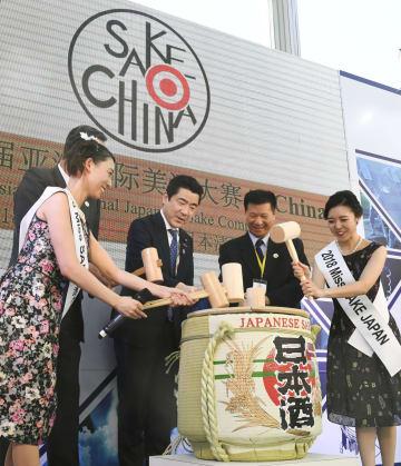 日中平和友好条約の締結40周年を記念した日本酒コンテストで、鏡開きをするミス日本酒の須藤亜紗実さん(右端)ら=24日、北京(共同)