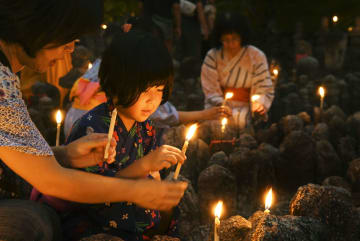 無縁仏を供養する「千灯供養」で、ろうそくをともす子ども=24日夜、京都市右京区