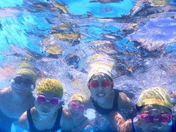 笑顔で泳ぐ子どもたち。県内は記録的な猛暑となった=23日、盛岡市上田(水中カメラで撮影)