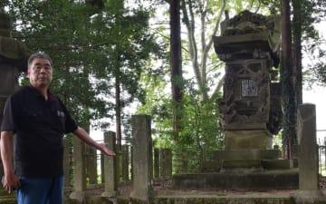 石造りの重厚な社殿と地元自治会の細岡さん=24日午後、大田原市加治屋