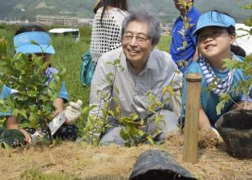 岩手県山田町で開かれた植樹祭で木を植える細川元首相(中央)ら=25日午前