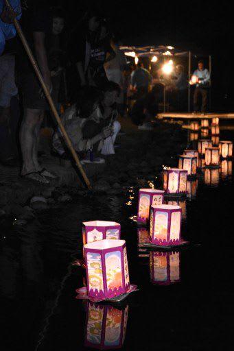 家族が見守る中、水路を流れゆく灯籠