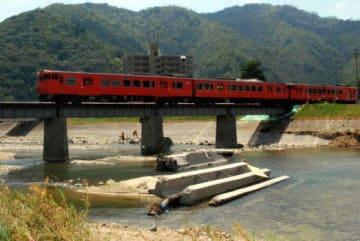 「第2三篠川橋梁」を通過する芸備線の点検列車。三篠川には流失した近くの鳥声橋の一部が残る(24日、広島市安佐北区上深川町)