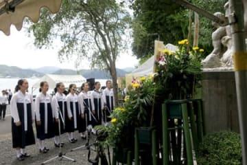 殉難の碑の前で追悼歌をささげる生徒たち(25日午前11時40分、舞鶴市佐波賀)