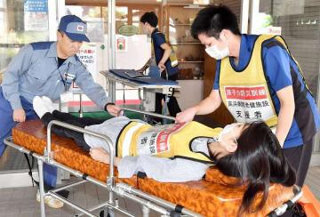 入所者の搬送訓練に取り組む関係者ら=8月25日午前11時25分ごろ、福井県高浜町の若狭高浜病院附属介護老人保健施設