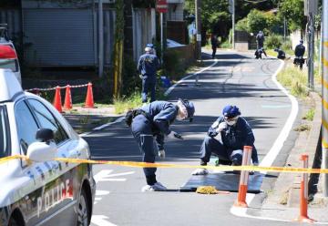 女性が男に刺された殺人未遂事件で、現場検証する県警の警察官ら=25日午前10時40分ごろ、船橋市