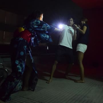プールサイドで来場客に襲い掛かる、浴衣姿のお化け役スタッフ(左)=柏市の「メガロスクロス柏24店」
