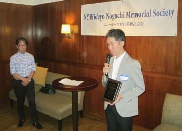 ニューヨーク野口英世記念会の奨学金を受けることが決まった園下将大さん。左は記念会の本間俊一会長=25日、ニューヨーク(共同)
