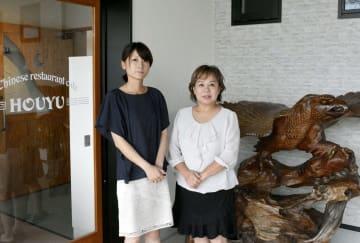 中華料理店「宝友」の入り口に立つ末野博子さん(右)と影野麻子さん。右の置物は被災前の宴会場に飾られていた=宇土市