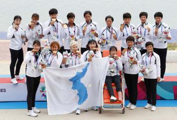 カヌー・スプリント女子のトラディショナルボート500メートルで金メダルを獲得し、記念撮影する南北合同チーム「コリア」=パレンバン(共同)