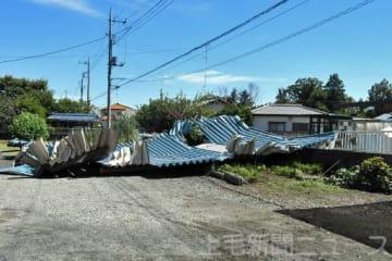 突風で飛ばされたトタン屋根。隣の民家のフェンスをなぎ倒した=26日午後0時半ごろ、邑楽町狸塚