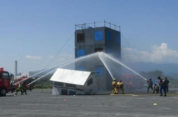 火災が発生したと想定した建物に協力して放水する日米の消防隊員=海老名市上郷の県立相模三川公園