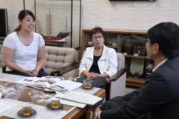 世界各地で被爆体験を証言し、田上市長に帰国報告する倉守さん(中央)=長崎市役所