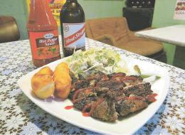 ジャマイカの代表的な料理「ジャークチキン」(900円)。「フェスティバル」と呼ばれる甘くないドーナツと一緒にいただきます
