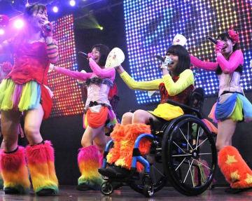 車いすに乗ったままパフォーマンスする猪狩ともかさん(右から2人目)=8月26日、東京都内