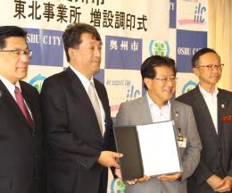 新生産棟建設の調印式に臨んだ佐々木社長(左から2人目)=奥州市役所