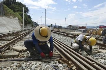 JR呉線水尻駅で行われた断線したケーブルを新しいものに取り換え敷設する復旧工事=28日午後、広島県坂町