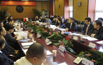 北京で開かれたEV充電器の規格統一に向けた日中業界団体の覚書調印式=28日(共同)