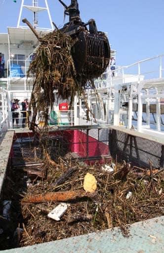西日本豪雨で瀬戸内海に流出した倒木やアシなどを回収する海面清掃船=7月19日