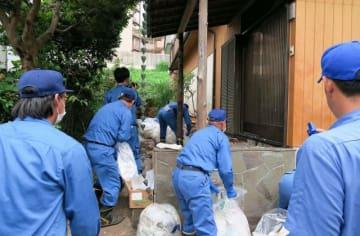 50代の男性の自宅の外に散乱したごみを集める作業員=横須賀市