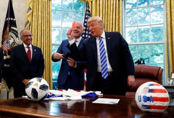 執務室でレッドカードを示すトランプ米大統領(右)とFIFAのインファンティノ会長(中央)=28日、ワシントン(ロイター=共同)