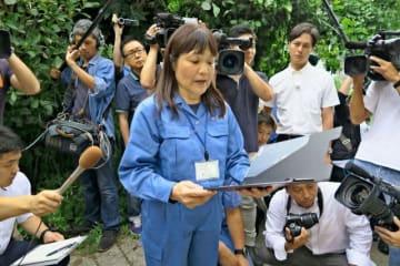 多くの報道陣に囲まれ、代執行宣言を読み上げる横須賀市の古谷久乃・福祉総務課長