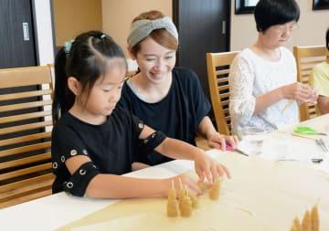 板状の蜜ろうを巻いてキャンドルを作る親子連れ=八代市