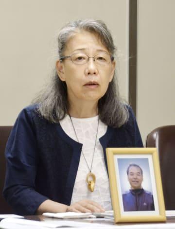 判決後、四條昇さんの遺影を前に記者会見する妻延子さん=29日午後、東京・霞が関の司法記者クラブ