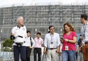 2020年東京パラリンピックに向け、建設中の新国立競技場周辺を視察する各国・地域のNPC代表ら=29日午後、東京都渋谷区
