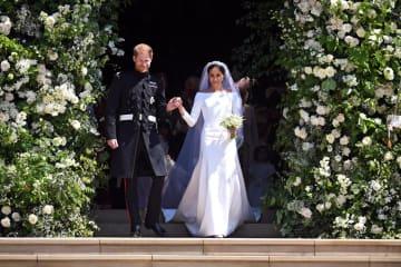 ウィンザー城の礼拝堂を出るヘンリー王子(左)とメーガン妃=5月19日、ロンドン郊外(ロイター=共同)