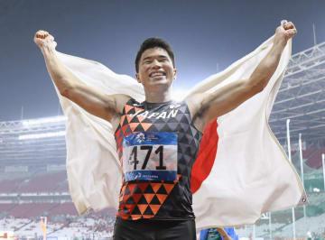 男子200メートルで優勝し、笑顔で日の丸を広げる小池祐貴=ジャカルタ(共同)