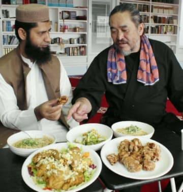 イスラム教の学者カーンさん(左)の指示を仰ぎながら、ハラル対応の料理を作る佐藤さん。テーブルに並ぶのはチキン南蛮や唐揚げなどの郷土料理