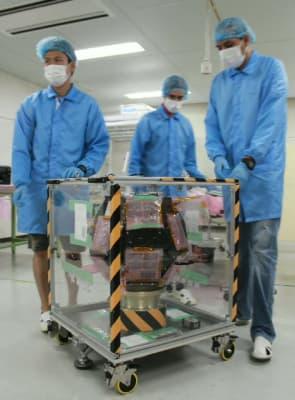 小型環境観測衛星「てんこう」を運び出す九工大大学院の学生=29日、北九州市
