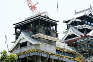 足場の土台となる赤い鉄骨が差し込まれた熊本城天守閣の小天守3階部分。右奥は大天守=29日、熊本市(上杉勇太)