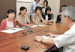 山田さん(右端)の体験に耳を傾ける柳谷さん(左から2人目)。テーブルに並ぶレコーダーが証言を記録する=7月20日、仙台市役所