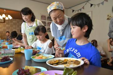 子ども食堂の食事と来夢のメンバーとの会話を楽しむ子どもたち=古河市大山