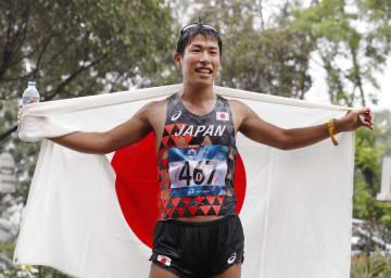 男子50キロ競歩で優勝し、笑顔で日の丸を広げる勝木隼人=ジャカルタ(共同)