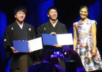 表彰式で賞状を手に喜ぶ名久井農の坂本さん(左)、大平さん。右はヴィクトリア皇太子=28日夜、スウェーデン・ストックホルム(日本河川協会提供)