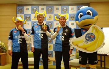 バナナのかぶりものを着用し、記念撮影する福田紀彦市長ら(右から2番目)=川崎市庁舎