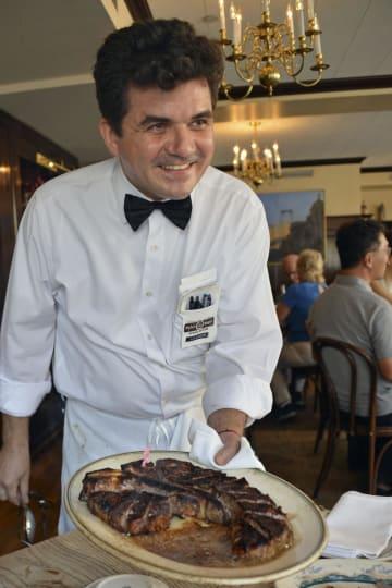 ニューヨークの「ピーター・ルーガー」本店で、最高級ステーキを見せるウエーター=16日(共同)