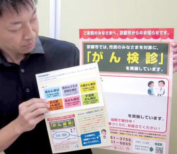 京都市が作製したがん検診のPRポスター。医療機関によって受診可能な検診の種類が異なるため、ポスターにシール(手前)を貼って伝える