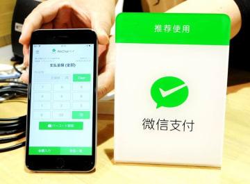 ウィーチャットペイが使えることを示す看板と、店側が使用する端末のアプリ画面=福井県勝山市のスーベニアショップラプトル