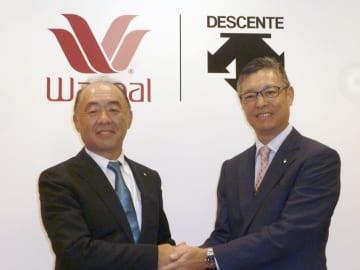 記者会見後に握手するワコールHDの安原弘展社長(左)とデサントの石本雅敏社長=30日、京都市