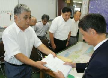 清水剛都市計画部長(右)に素案を手渡す麻生金次代表=30日、大分市役所