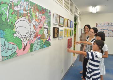 佐久間一行さんのアート展を楽しむ親子=水戸市宮町