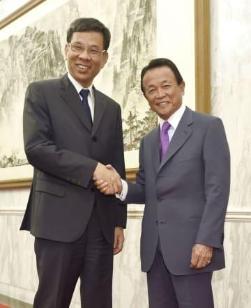 握手する麻生財務相(右)と中国の劉昆財政相=31日、北京の釣魚台迎賓館(共同)