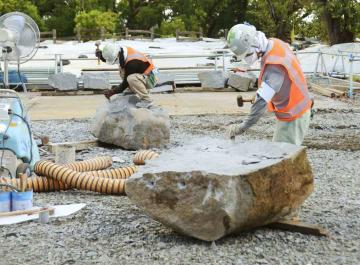 報道陣に公開された、熊本城・大天守の崩れた石垣の積み直しに使う石材の加工現場=31日午前、熊本城