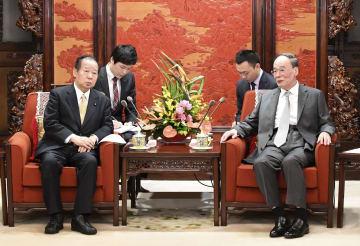 中国の王岐山国家副主席(右)と会談する自民党の二階幹事長=31日、北京の中南海(共同)